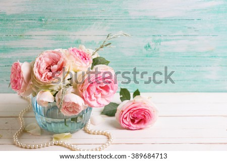 Pink roses flowers  in blue vase on white painted wooden background against turquoise wall. Selective focus. Place for text. - stock photo