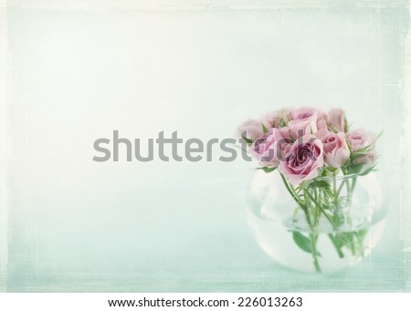 Pink roses in a glass vase filled with water on light blue background with vintage textured editing - stock photo