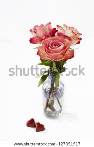 Pink roses in vase and heart shaped chocolates on white - stock photo