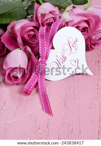 Pink Roses on pink wood background closeup with Happy Valentines Day heart shape gift tag, vertical with copy space. - stock photo