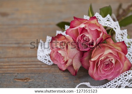 Pink roses with white lace on wooden background - stock photo