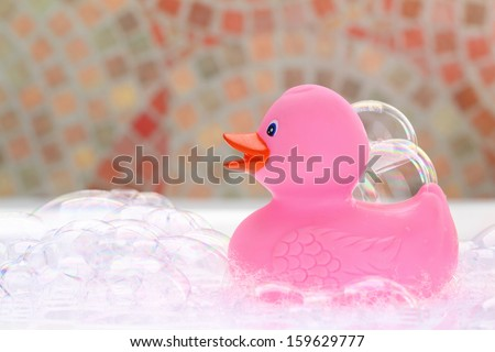 Pink rubber duck in bath foam - stock photo
