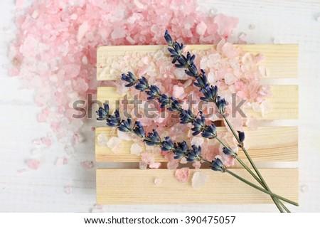 Pink sea salt with lavender aroma. Scattered bath salt, lavender dried flower. - stock photo
