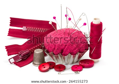 Pink sewing accessories: thread, needle, buttons, thimble, zipper and pincushion - stock photo