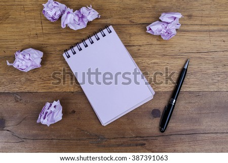 Pink sheets notebook with spiral in the center of the wooden dark brown table with black pen on side and crumpled paper from above - stock photo