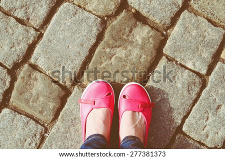 Pink shoes and jeans legs - stock photo