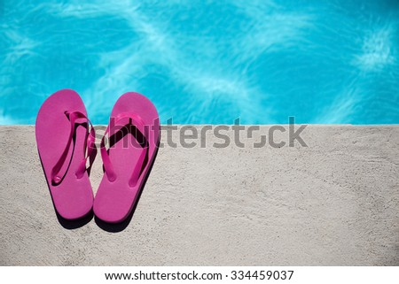 Pink slippers near swimming pool at poolside - stock photo