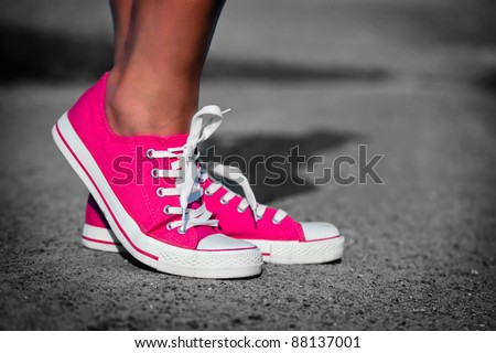 Pink sneakers on girl, young woman legs, outdoors in black and white - stock photo
