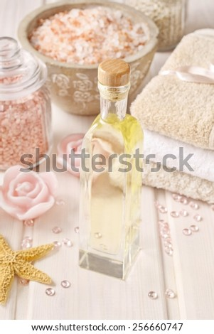 Pink spa set: bottle of rose essential oil, towels and sea salts - stock photo