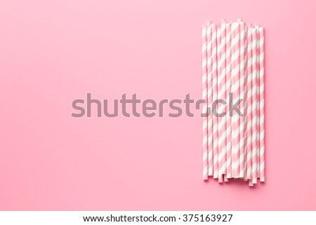 pink striped straws on pink background - stock photo