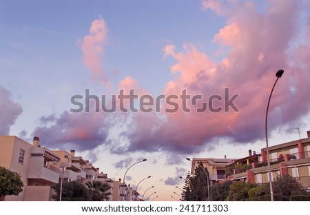 pink sunset over Fertilia on a cloudy day - stock photo