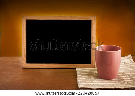 Pink Tea cup and chalkboard on wooden table - stock photo