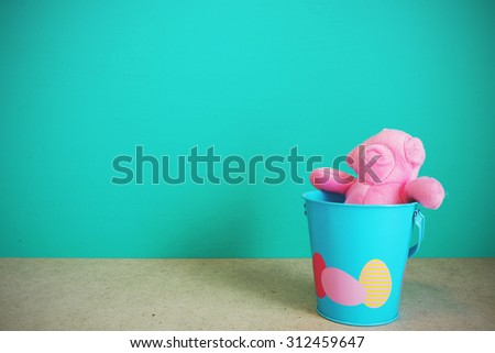 Pink Teddy bear in blue cup on table front mint green background. Vintage effect. - stock photo