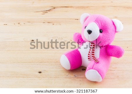 Pink teddy bear toy on wood background. - stock photo