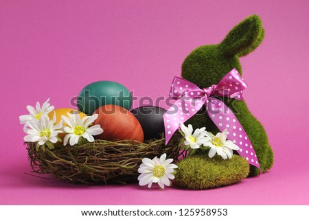 Pink theme Happy Easter scene still life with grass bunny rabbit with rainbow color eggs in a nest with white daisies. - stock photo