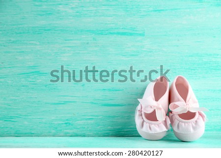 Pink toddler shoes on wooden background - stock photo