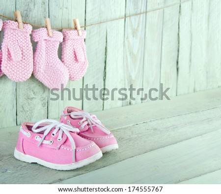 Pink toddler shoes on wooden light green vintage background with copy space - stock photo