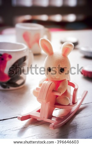 Pink toy rabbit sitting on rocking horse .Processed with vintage style. Shallow depth of field. - stock photo