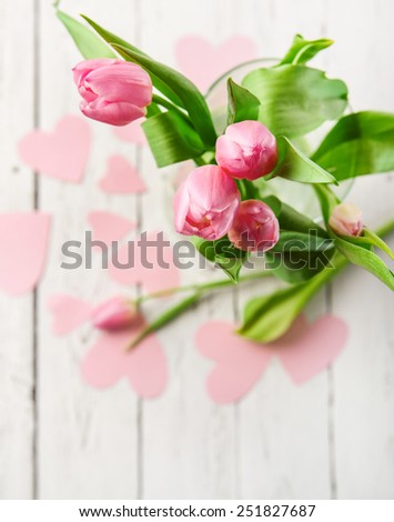 Pink tulips bouquet in vase on white wooden table - stock photo