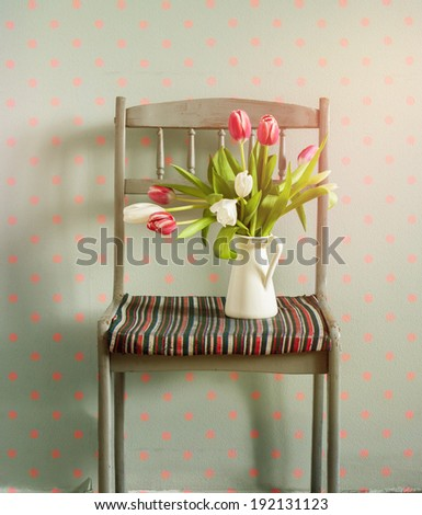 Pink Tulips on a Chair, Flowers in Spring Composition on Grey Wall with Pink Pears. seasonal home interior - stock photo