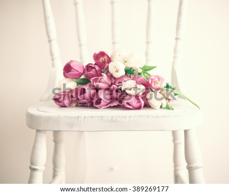 Pink tulips over a white and french wood chair - stock photo
