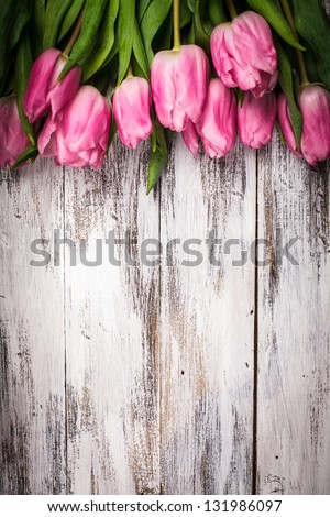 Pink tulips over shabby white wooden table - stock photo
