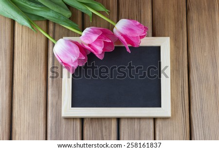 Pink tulips with empty blackboard on wooden background - stock photo