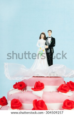 Pink wedding cake with red roses and couple on top on blue background - stock photo