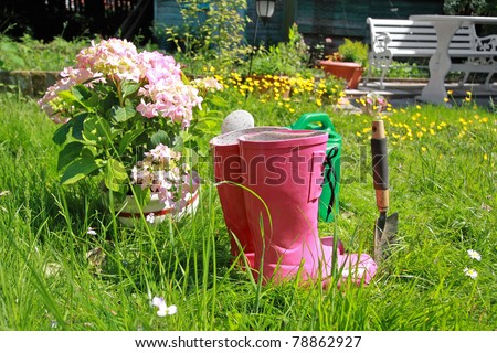 Pink wellingtons in the Spring garden - stock photo