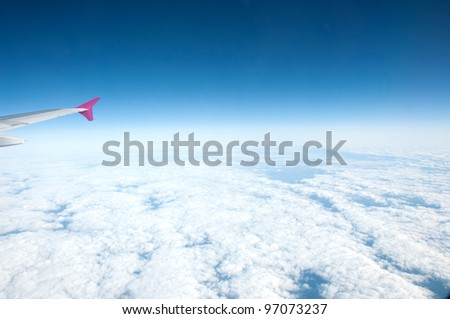 pink wing aircraft above the clouds - stock photo
