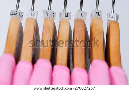 Pink women's t-shirts hang on wooden hangers with indexes of the XXS, XS, S, M, L, XL, XXL sizes on a light background. - stock photo