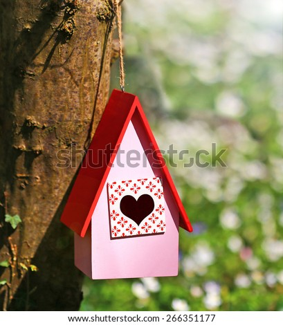 Pink wooden country  birdhouse with a red roof and heart entrance hangs on a tree in spring forest on blurred background - stock photo