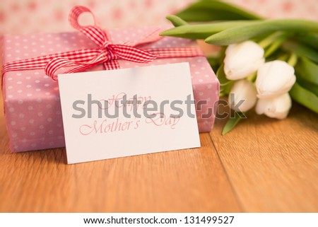 Pink wrapped present with bunch of white tulips and mothers day card on wooden table - stock photo