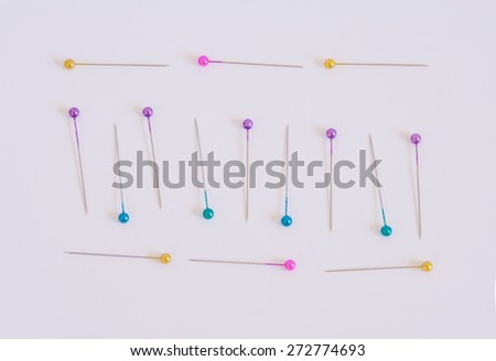 Pink, yellow, blue, purple sewing pins arranged on a white background. - stock photo