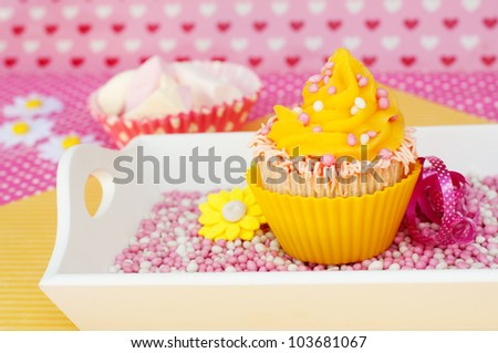 pink yellow cupcake on a plateau with marshmallows in the background - stock photo