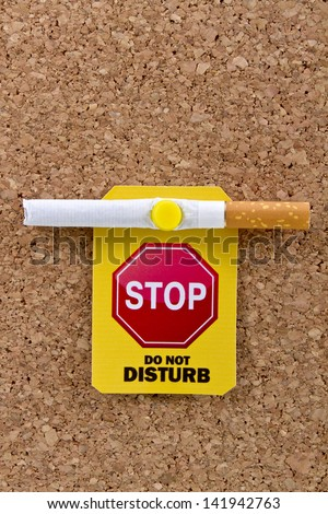 Pinned to cork board filter cigarette with a yellow do not disturb label.Stop smoking concept. - stock photo