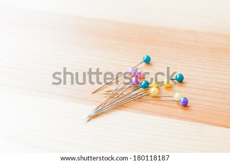 Pins with colourful heads on wooden table - stock photo