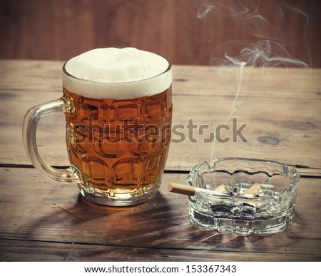 Pint of Beer and a lit cigarette  - stock photo