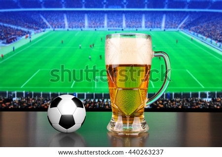 Pint of beer and ball before tv showing soccer - stock photo