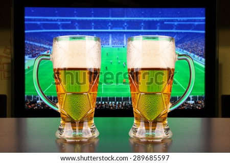 Pint of beer before tv showing soccer - stock photo
