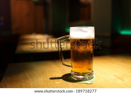 Pint on a wooden table at a pub - stock photo