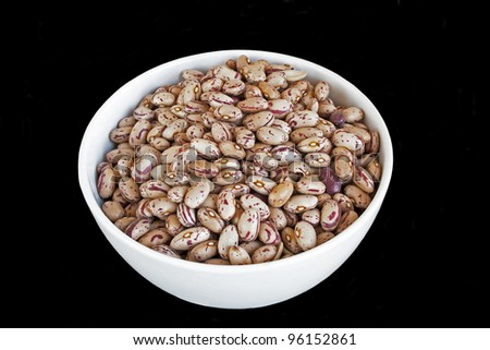 Pinto beans in white bowl  isolated over black  background - stock photo