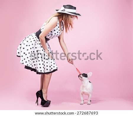 Pinup fashionable woman posing with cute pug dog. Pink background. - stock photo