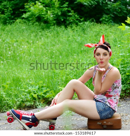 Pinup girl sitting on suitcase with retro roller skates and give kisses, portrait of young happy sexy woman in pin-up style over park nature outdoor - stock photo
