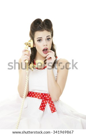 Pinup girl with her hair down in retro victory rolls, talking on the phone and looking surprised. - stock photo