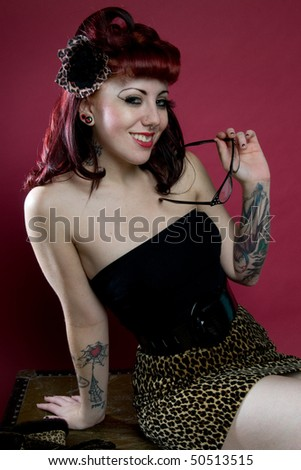 pinup girl with tattoos sitting on antique trunk - stock photo