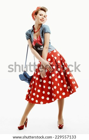 Pinup young woman in vintage American style isolated on white studio background, dressed in a red dress with polka dots and denim vest - stock photo