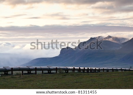 Pipeline along side Dalton highway with mountain as a background - stock photo