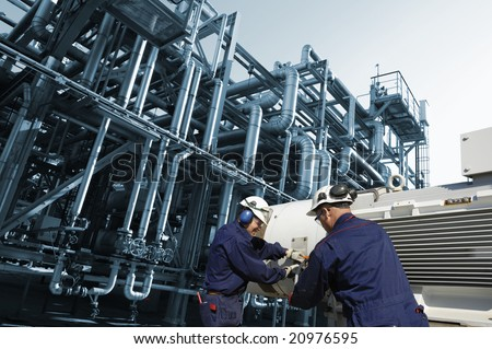 pipeline complex with two engineers working on machinery, inside oil refinery action. - stock photo