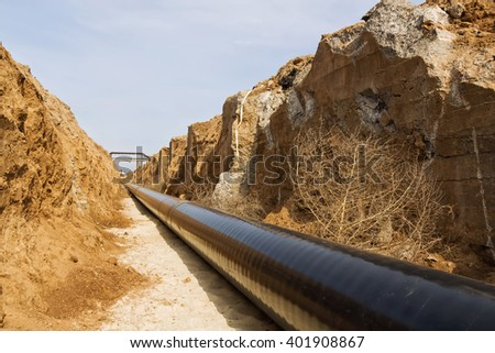 pipeline is in the protective insulation laid on the bottom of the trench dug - stock photo